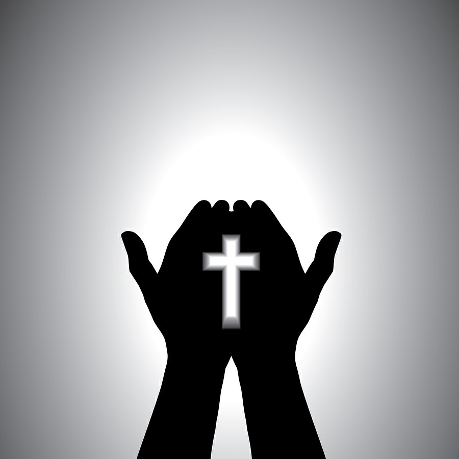 Devout christian worshipping with cross in hand