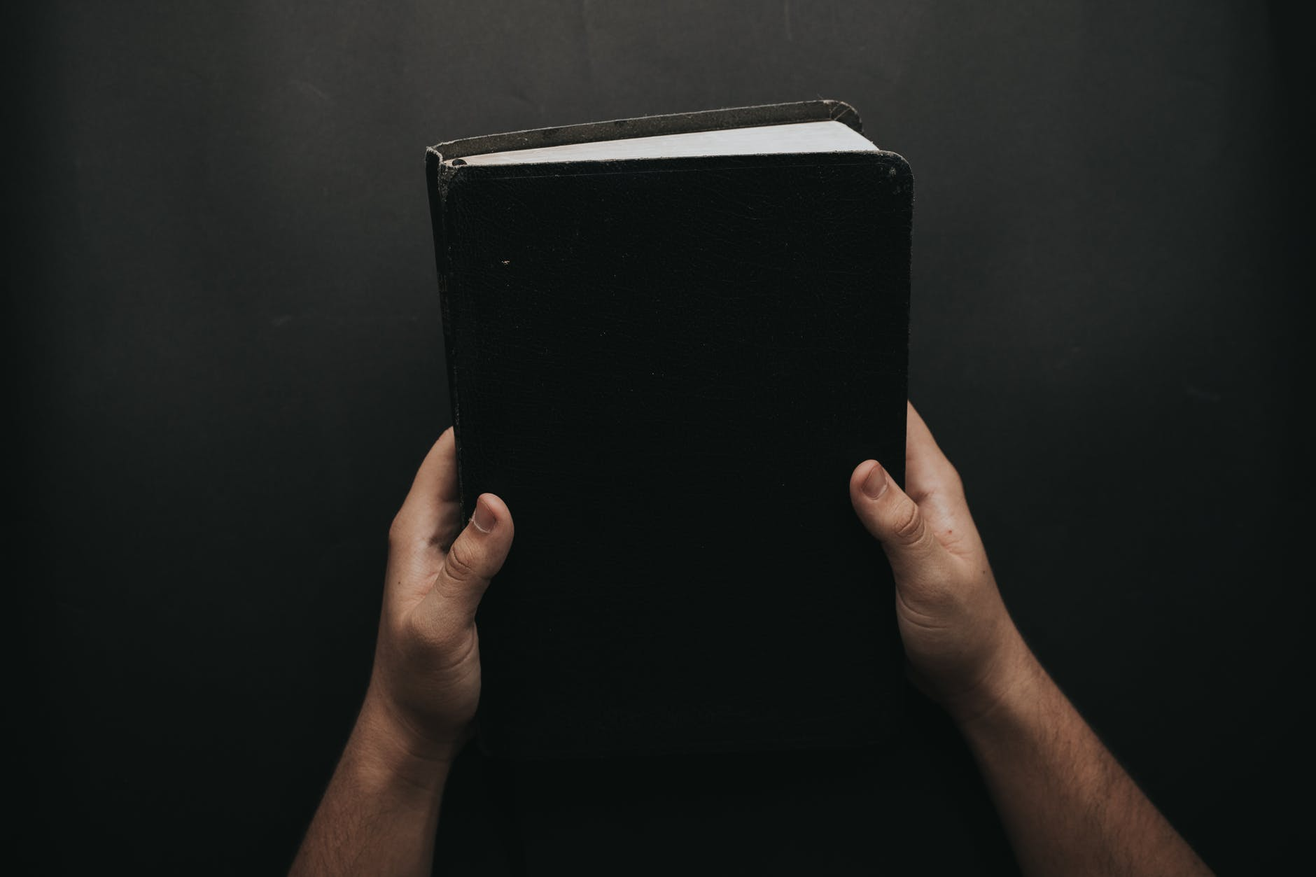 person holding black cover bible